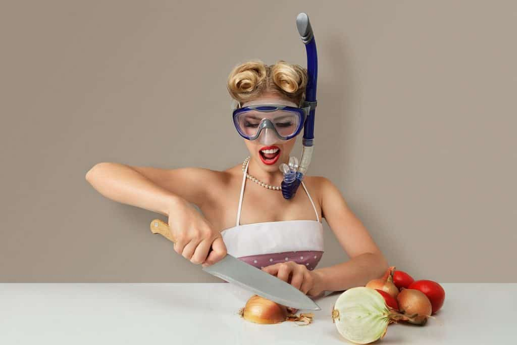 Young woman cutting onion in diving mask