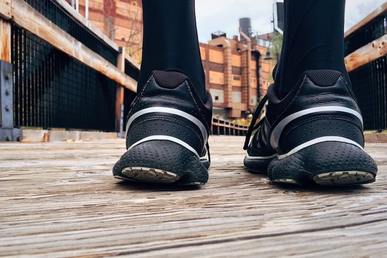 The heels of sports shoes with a background of industrial style boardwalk