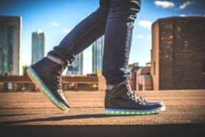 lower legs and lit up shoes walking on concrete town scene