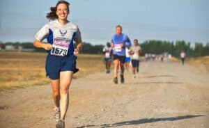 Smiling running woman in front in a marathon