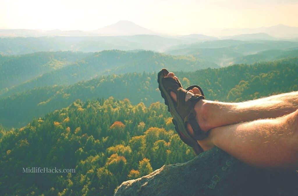 Long tired naked legs in hiking sandals on peak. Hiking in sandstone rocks, hilly landscape
