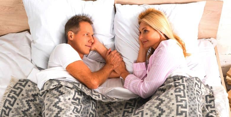 Mature couple in bed looking at each other and holding hands